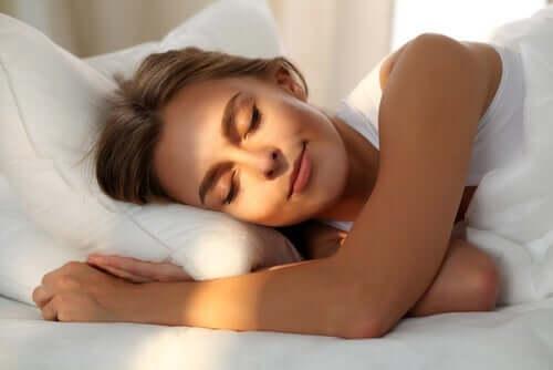 Uyurken yüzüne güneş vuran bir kadın.