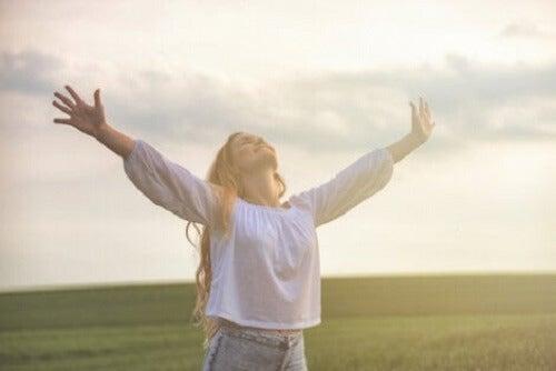 Kollarını gökyüzüne doğru açmış, gülümseyen bir kadın.