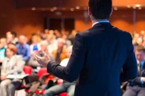 Bir kalabalığın önünde konuşma yapan bir adam.