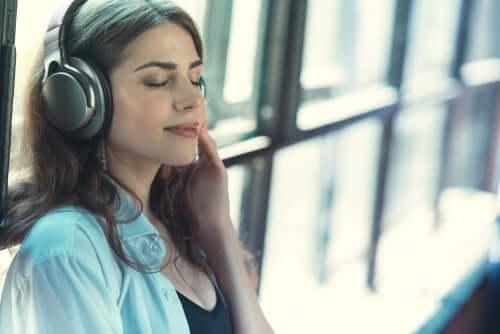 Kulaklıklarında bir şey dinleyen bir kadın.