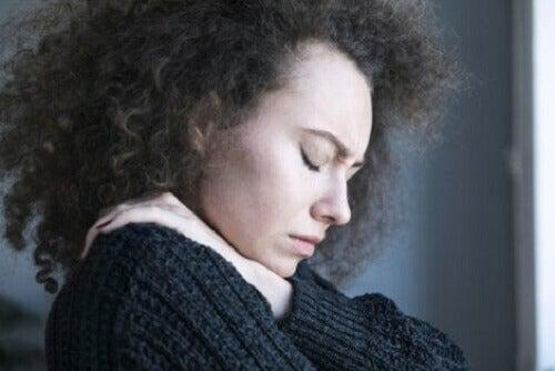 Gözleri kapalı, üzgün görünen bir kadın.