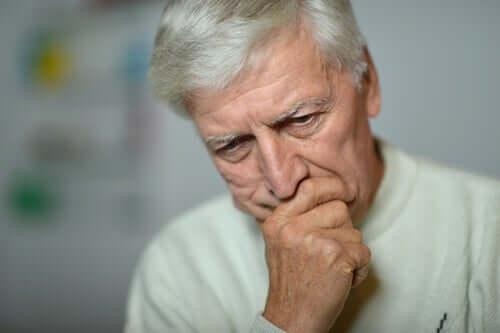 Üzgün görünen yaşlı bir adam.