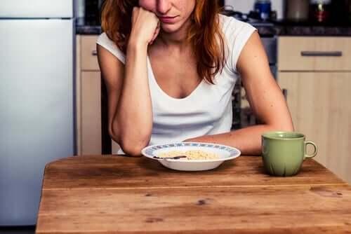 Önündeki yiyeceklere bakan bir kadın.