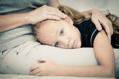 annesinin kucağına yatan kız çocuğu