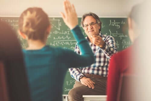 Derste masasına oturmuş el kaldıran öğrencilere söz veren hoca