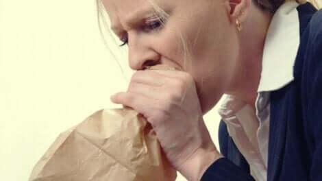 hiperventilasyon ile anksiyete: kağıt torbaya nefes alan kadın