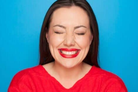 kırmızı kazaklı kadın gülümsüyor ve gözlerini kapatıyor