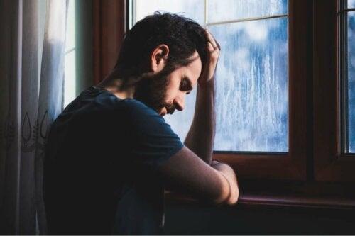üzgün adam pencerenin kenarında duruyor