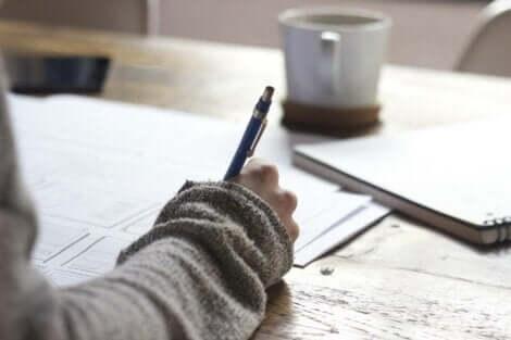 yazı yazan el ve kahve bardağı