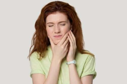 yüzü ağrıyan kadın eliyle yanağını tutuyor