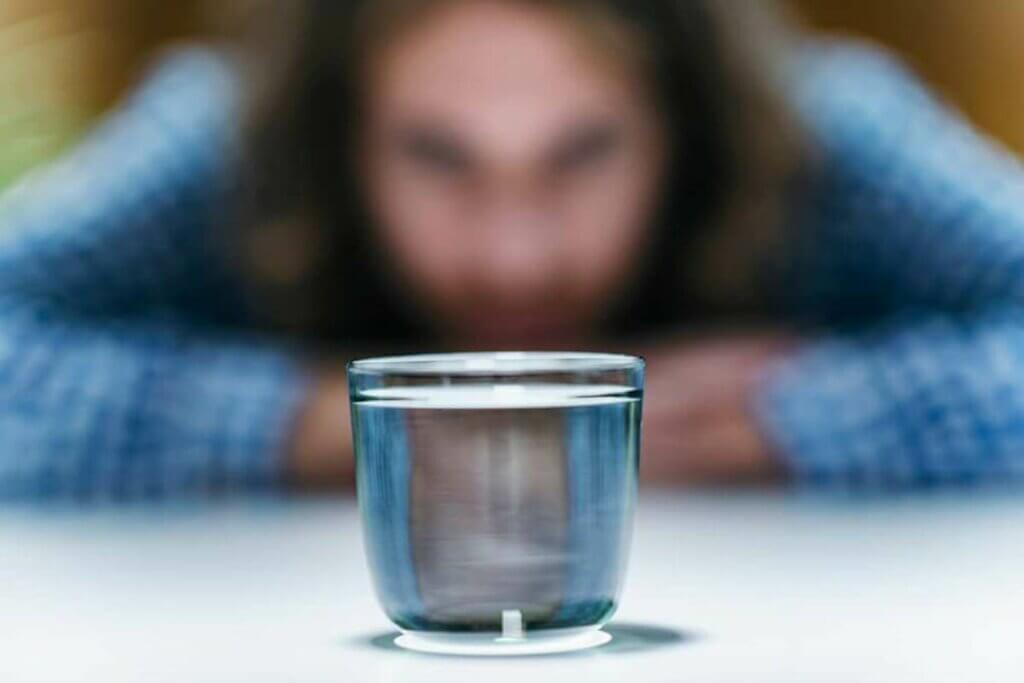 bir bardağın karşısında oturan kadın