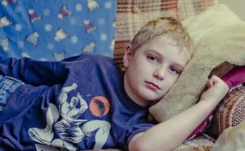 Kanepede yatan üzgün bir çocuk.