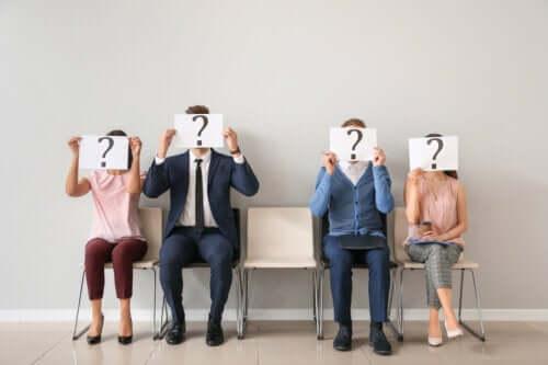 Yüzlerinin önünde soru işaretleri tutan insanlar.