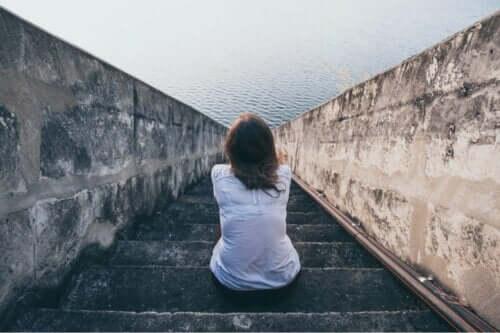 Yalnız başına, denize bakarak oturan bir kadın.