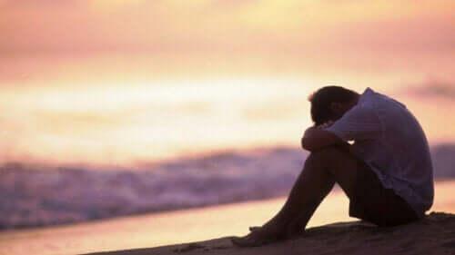 Sahilde yalnız başına oturan bir kişi.