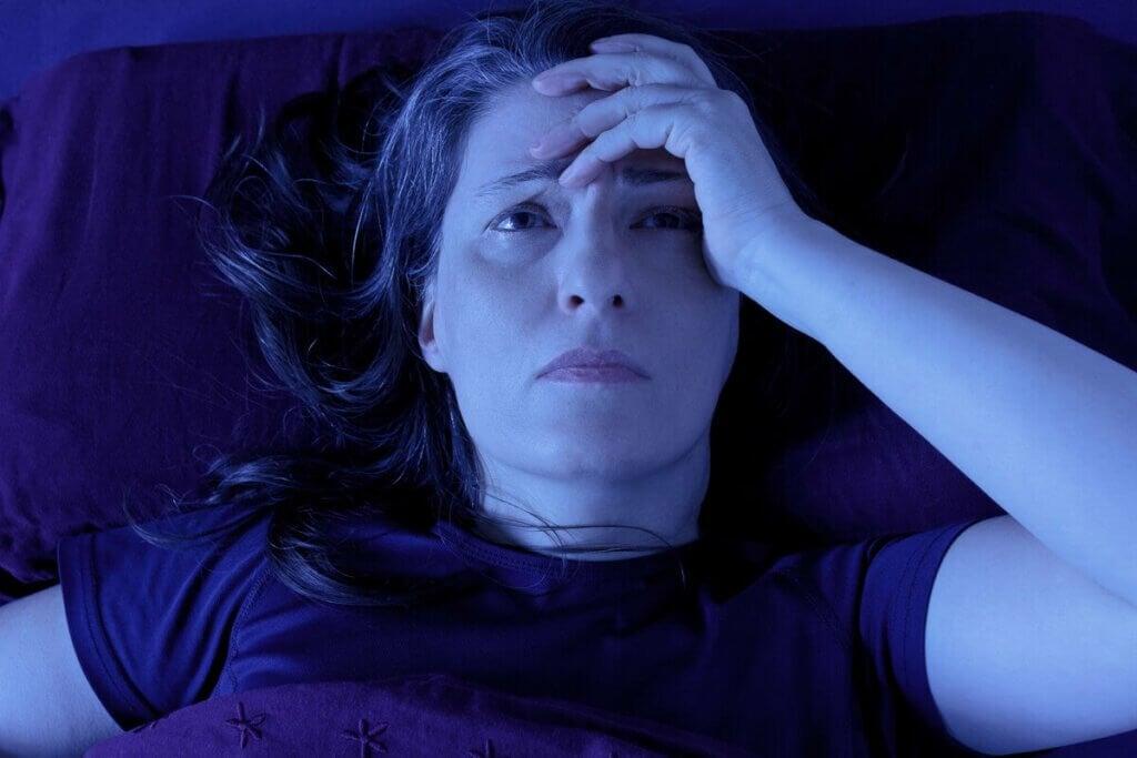 yatakta başı ağrıyan bir kadın