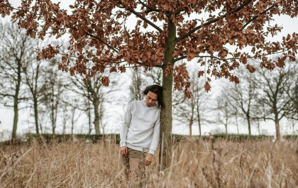 ağaca yaslanmış bir çocuk
