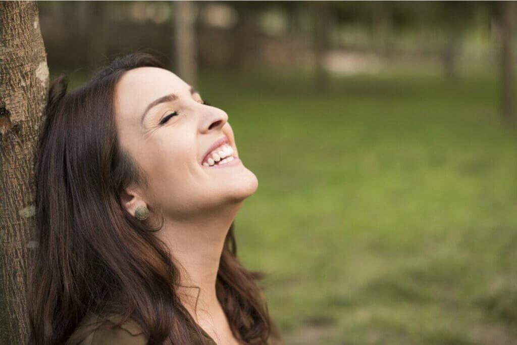 kafasını ağaca yaslamış mutlu bir kadın
