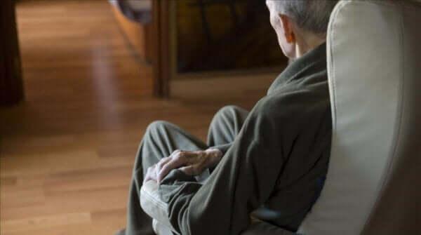 Kanepede oturan ve istemsiz hareketler yapan adam.