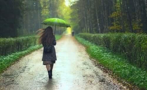 yağmurlu günde yeşil şemsiyeyle ormanlık alanda yürüyen kadın