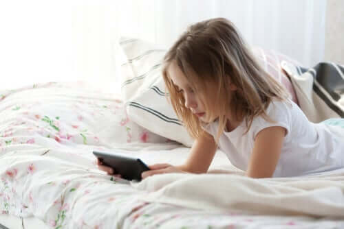 yatakta tablete bakan bir kız
