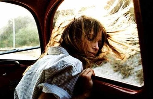 açık araba camından bakarken saçları rüzgarda savrulan kadın