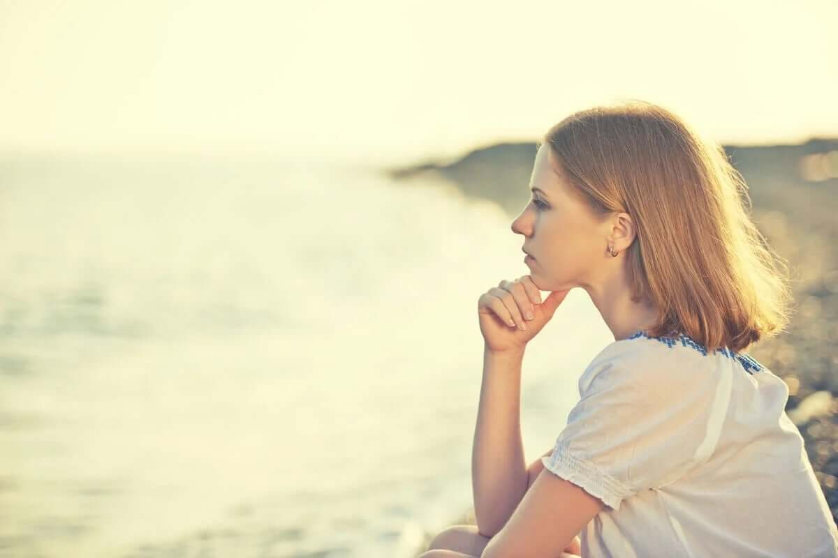 deniz kıyısında oturmuş düşünen kadın
