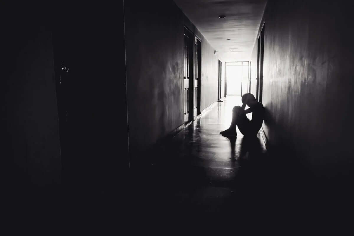 karanlık koridorda oturan üzgün genç