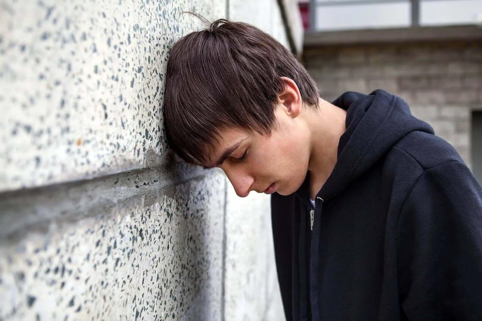 başını duvara yaslamış çocuk