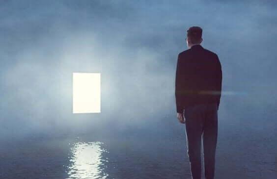 sislerin içindeki ışıklı kapıya bakan adam