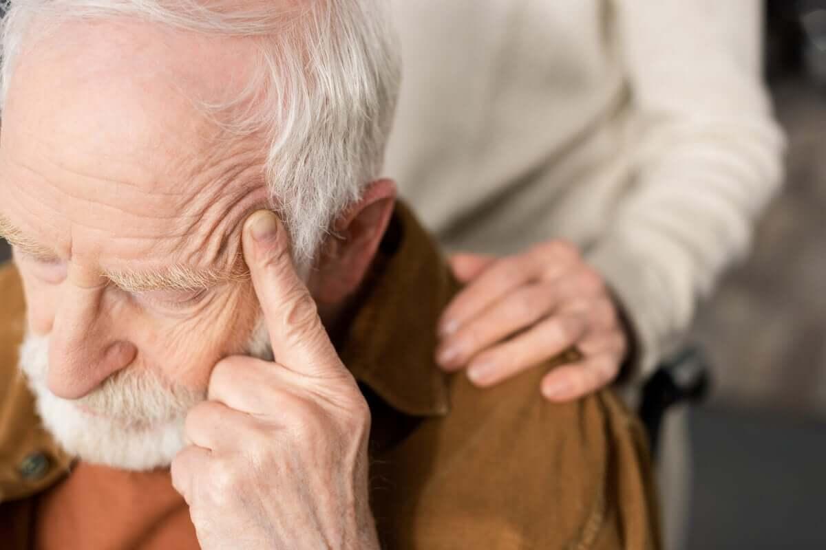 şakağını tutan yaşlı adam