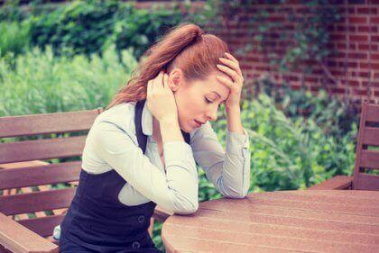 başı ağrıyarak masada oturan kadın