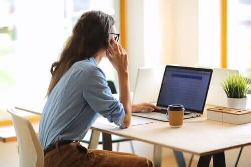 masasında oturmuş bilgisayarda çalışan kadın