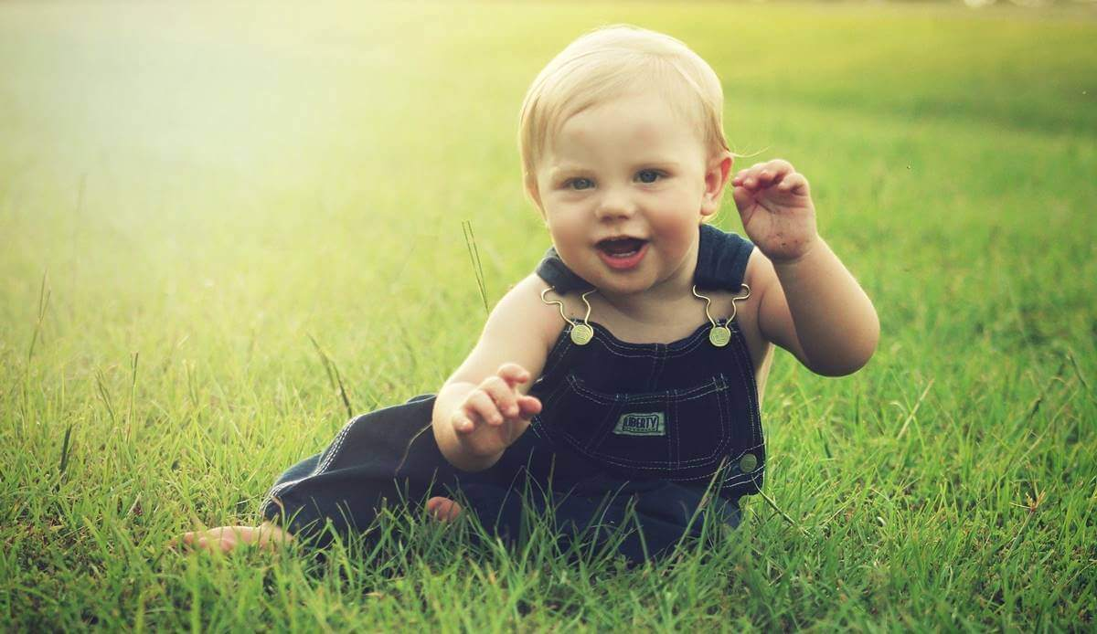 çimlerde oturan mutlu bebek