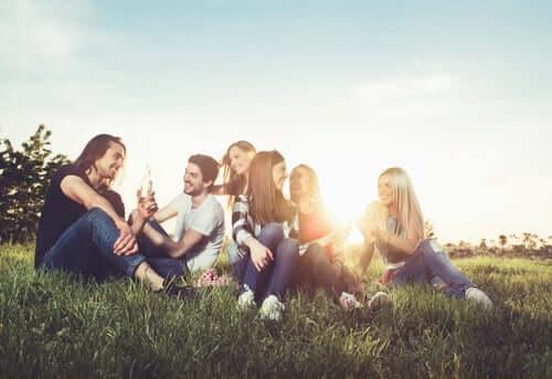 çimlerde oturmuş muhabebt eden gençler