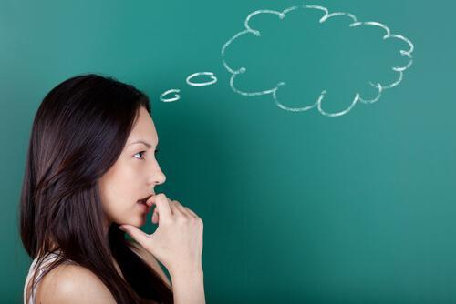 arkasındaki tahtada düşünce bulutu olan kadın