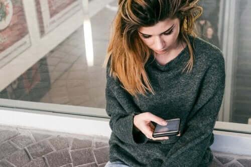 telefonuyla ilgilenen genç kadın