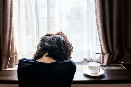 camın önünde başı ağrıyan kadın