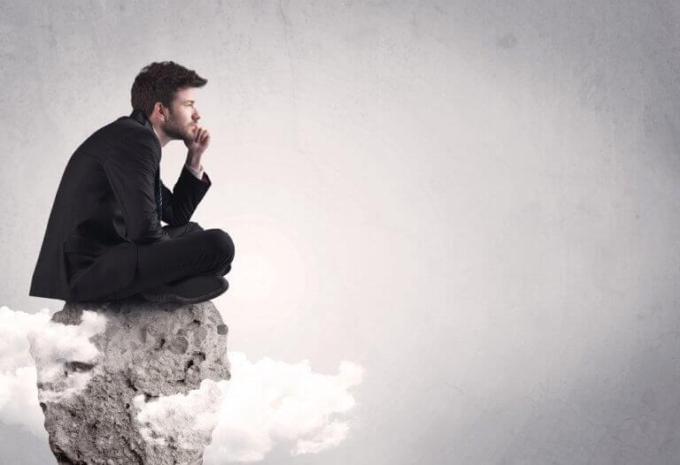 kayaya çömelmiş düşünen adam