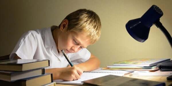 masa lambasının ışığında ödev yapan çocuk