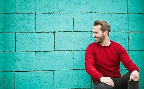 mavi duvarın önünde oturmuş gülümseyen kırmızı kazaklı adam