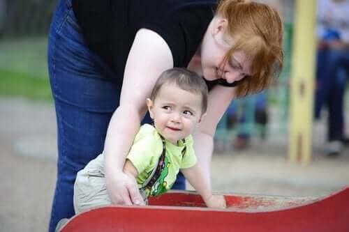 parkta bebeğiyle oynayan anne