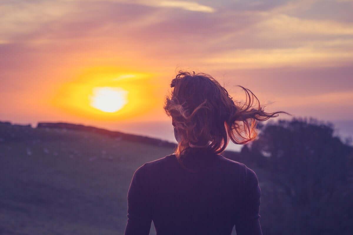 rüzgarda günbatımına bakan kadın