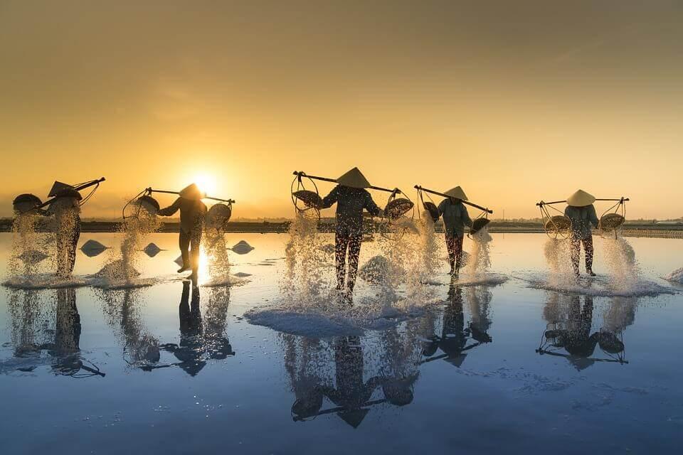 suda sırtlarında çubukla eşya taşıyan insanlar