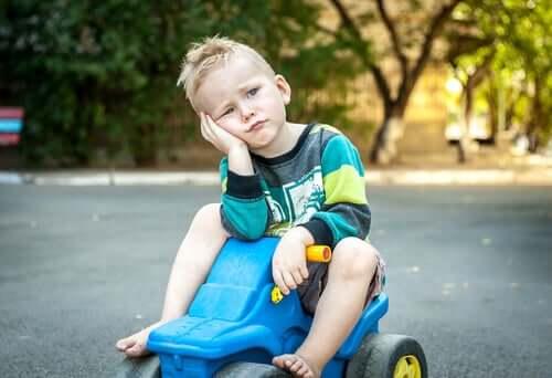bisikletinde canı sıkkın oturan çocuk