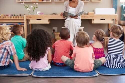 kitap okuyan öğretmeni dinleyen çocuklar