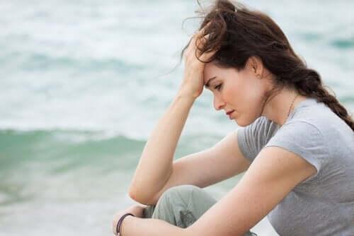 deniz kıyısında oturan hüzünlü ve düşünceli kadın