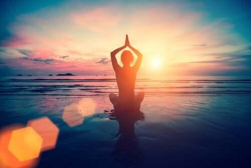 denizde gün batımında yoga yapan figür