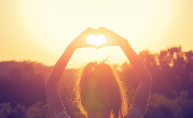 batan güneşe parmaklarıyla kalp yapan kişi
